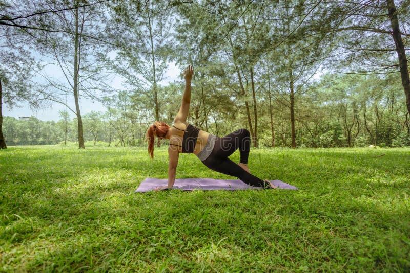 Mujer asiática que hace la yoga al aire libre imagen de archivo libre de regalías