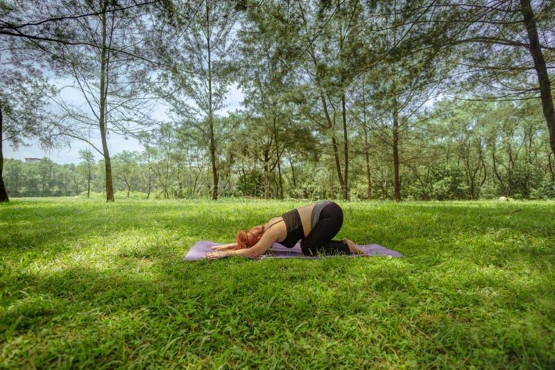 Mujer asiática que hace la yoga al aire libre fotografía de archivo