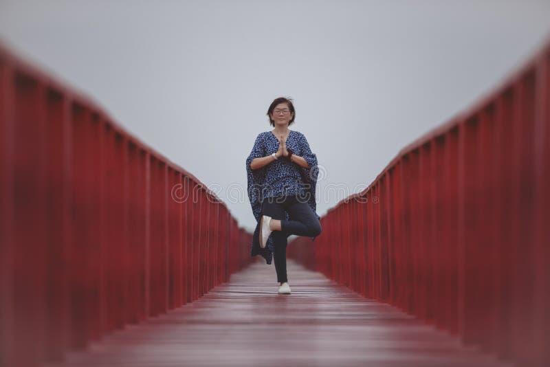 Mujer asiática que juega actitud de la yoga en el puente de madera rojo imagen de archivo