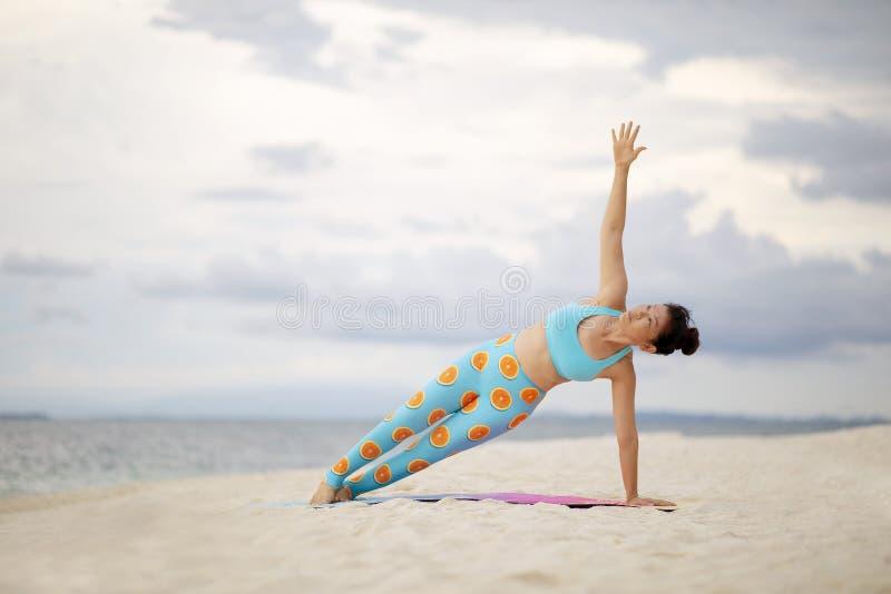 Mujer asiática que juega actitud lateral de la yoga del tablón en la playa blanca de la arena imagen de archivo