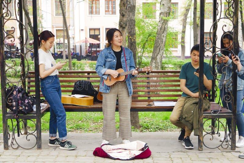 Mujer asiática que juega en la guitarra imagen de archivo libre de regalías