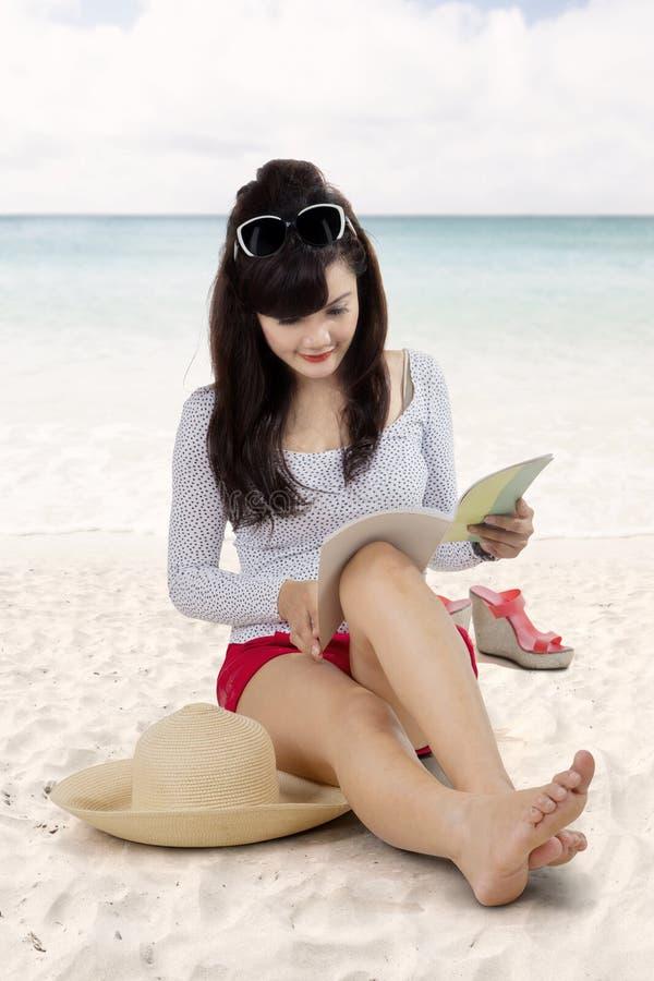 Mujer asiática que lee un libro en la playa imagenes de archivo