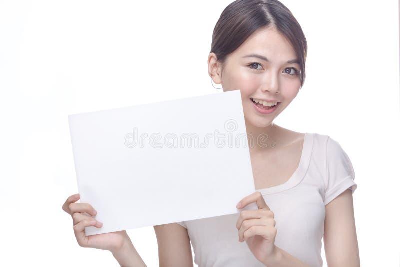 Mujer asiática que lleva a cabo la muestra en blanco fotos de archivo libres de regalías