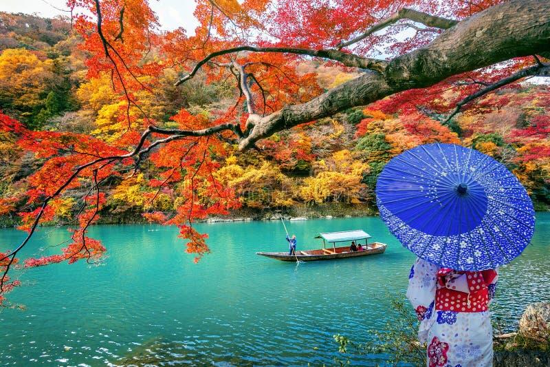 Mujer asiática que lleva el kimono tradicional japonés en Arashiyama en la estación del otoño a lo largo del río en Kyoto, Japón fotografía de archivo