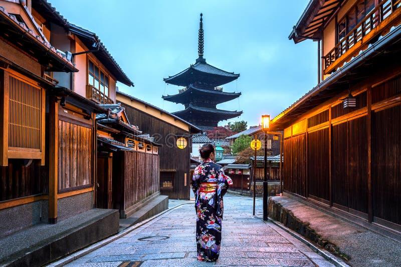 Mujer asiática que lleva el kimono tradicional japonés en la pagoda de Yasaka y la calle de Sannen Zaka en Kyoto, Japón imagen de archivo