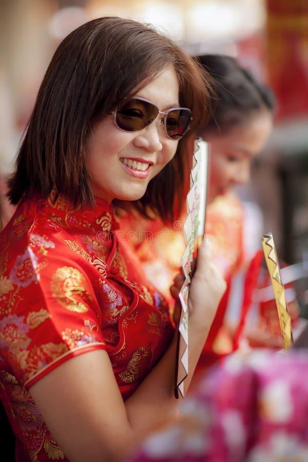 Mujer asiática que lleva el traje chino de la tradición y que sostiene la fan de bambú con la cara sonriente dentuda en ciudad de imagenes de archivo