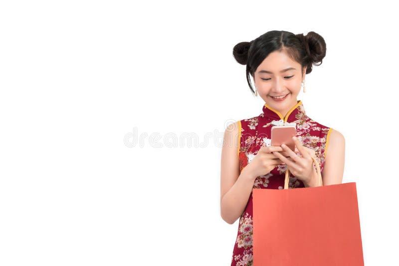 Mujer asiática que lleva el vestido chino con el smartphone móvil que hace compras en línea imagenes de archivo