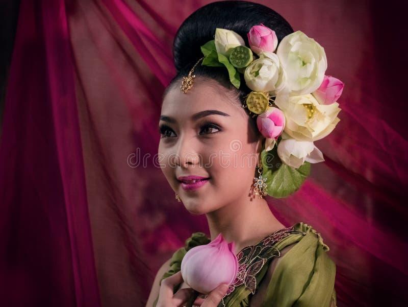 Mujer asiática que lleva la mano tradicional tailandesa del vestido que sostiene el loto la Florida fotos de archivo libres de regalías