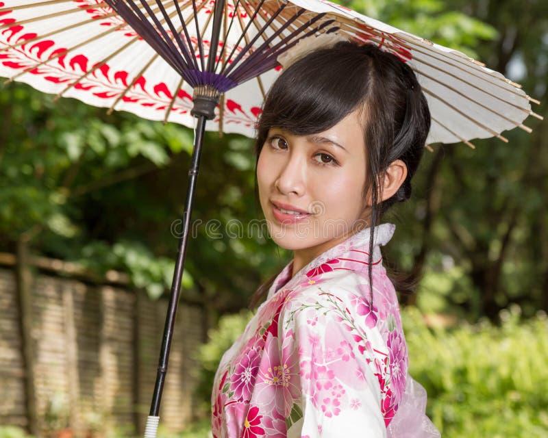 Mujer asiática que lleva un kimono que se sienta en jardín japonés imágenes de archivo libres de regalías