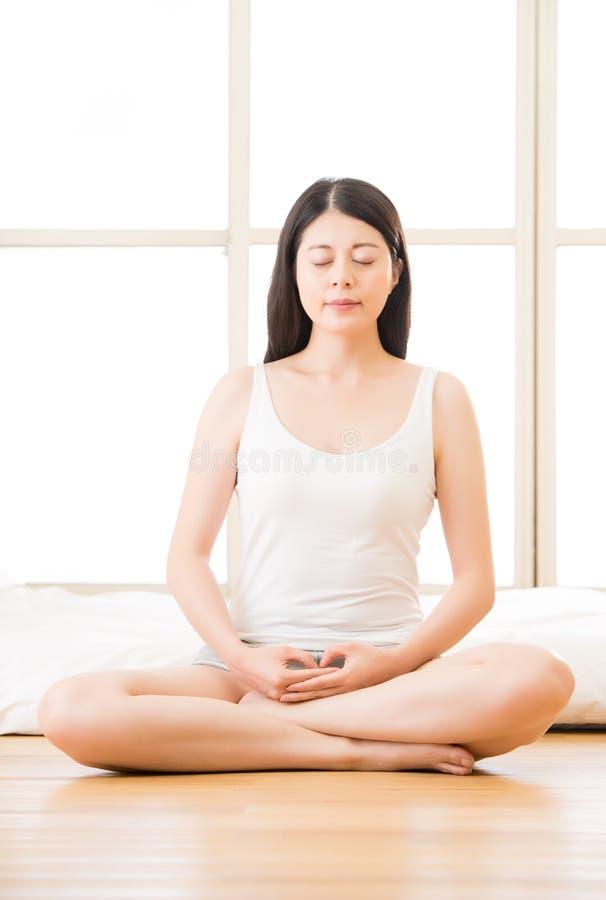 Mujer asiática que medita zen por mañana al lado de la cama fotografía de archivo