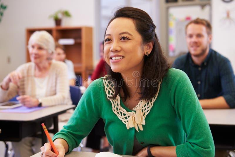 Mujer asiática que mira al tablero en una clase de la enseñanza para adultos fotografía de archivo