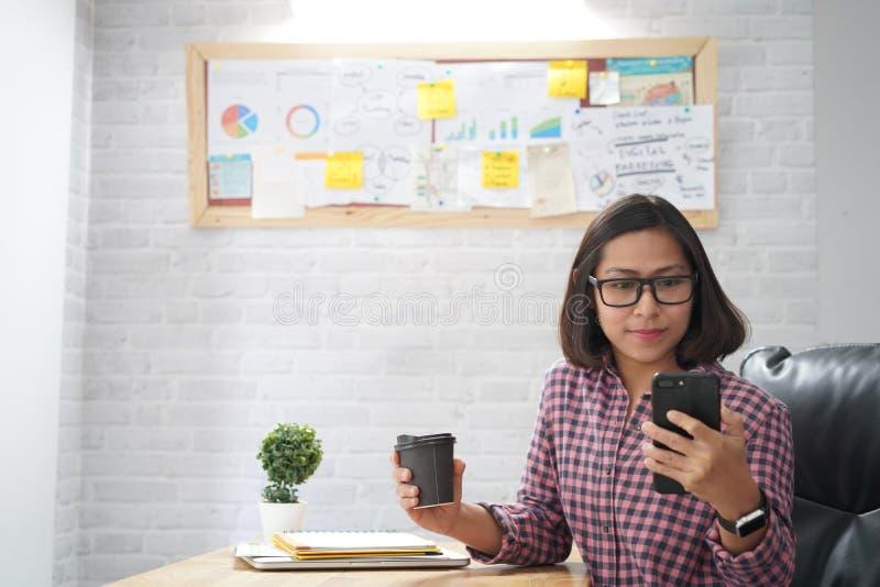 Mujer asiática que mira el teléfono elegante imagenes de archivo