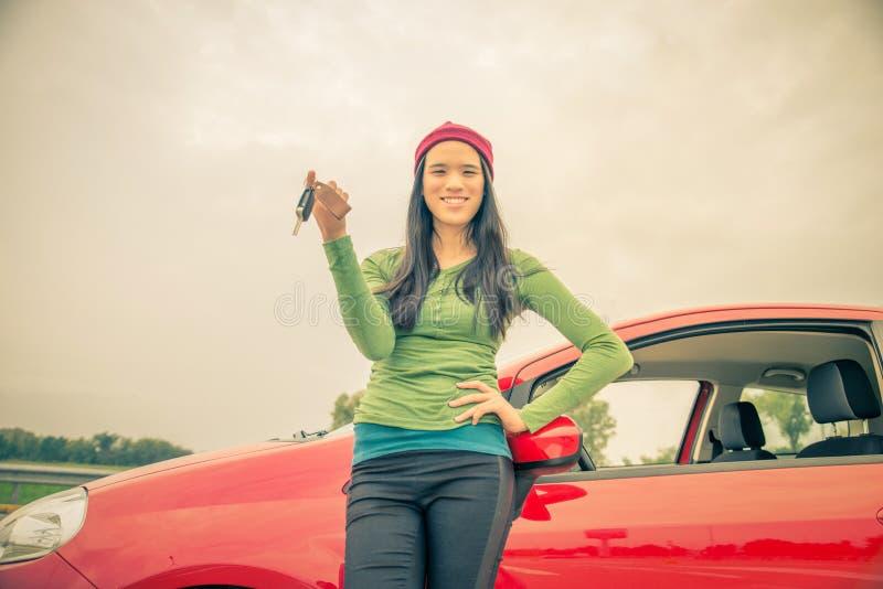 Mujer asiática que muestra llaves del coche imágenes de archivo libres de regalías