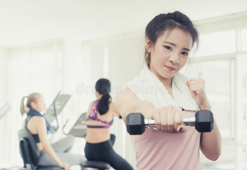 Mujer asiática que perfora la pesa de gimnasia adelante en aptitud fotos de archivo libres de regalías