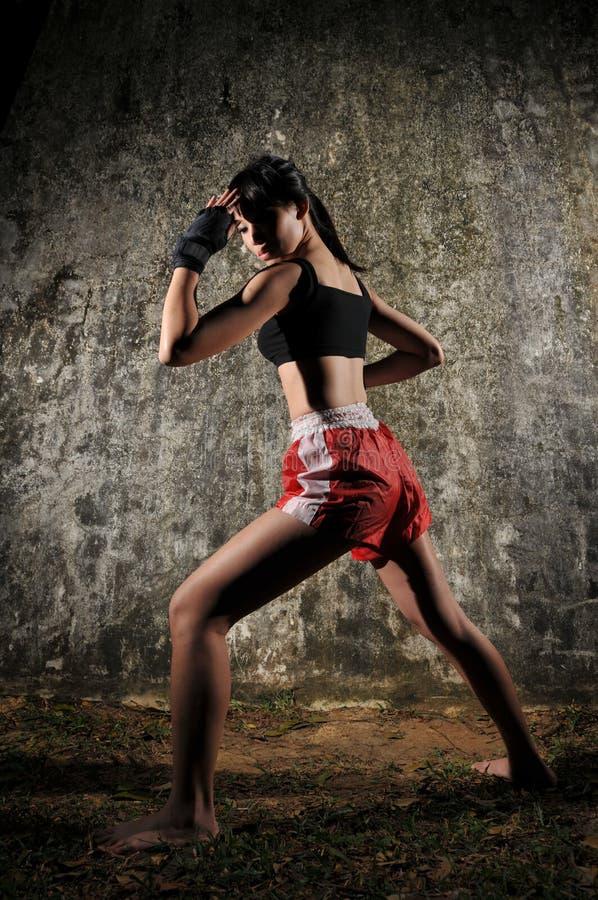 Mujer asiática que practica el boxeo tailandés de Muay foto de archivo
