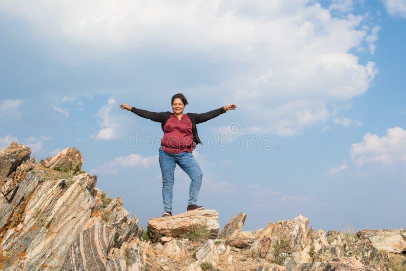 Mujer asiática que se coloca en rocas coloridas con sus brazos para arriba en la a imagen de archivo