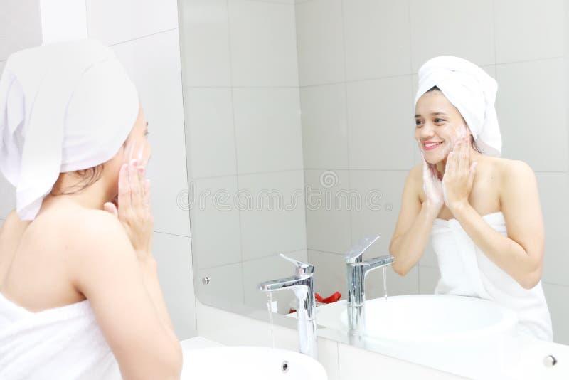 Mujer asiática que se lava la cara con un jabón imagen de archivo libre de regalías