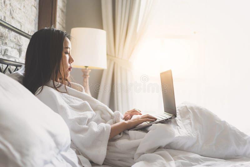 Mujer asiática que se relaja en la habitación y que trabaja en el ordenador portátil fotos de archivo libres de regalías