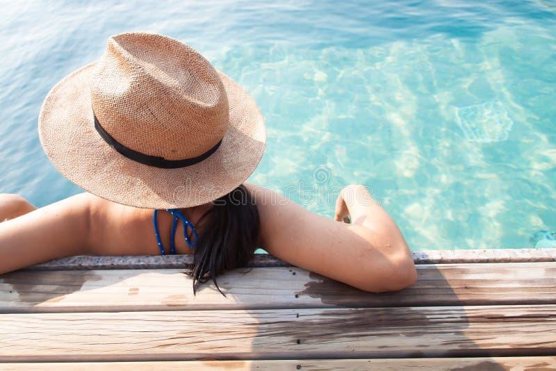 Mujer asiática que se relaja en la piscina, concepto de las vacaciones del viaje fotografía de archivo