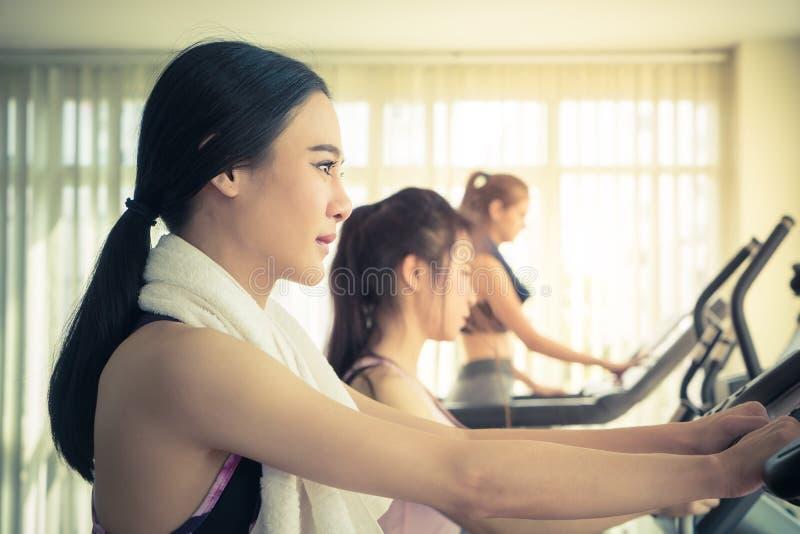 Mujer asiática que se resuelve en máquina del gimnasio de la aptitud imagenes de archivo