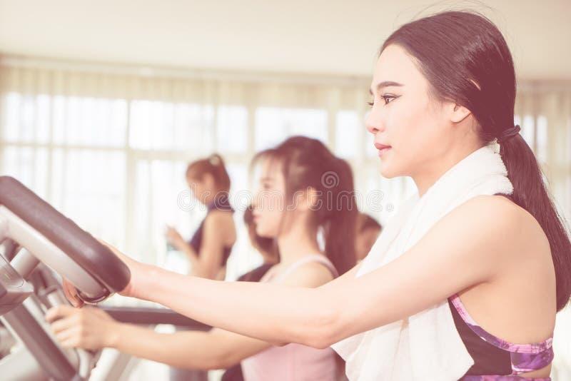 Mujer asiática que se resuelve en máquina del gimnasio de la aptitud imágenes de archivo libres de regalías