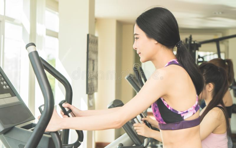 Mujer asiática que se resuelve en máquina del gimnasio de la aptitud foto de archivo