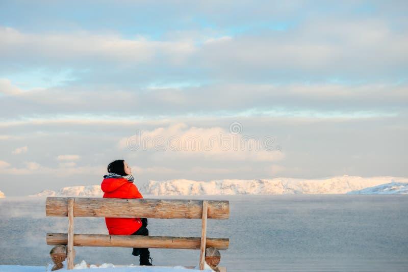 Mujer asiática que se sienta en banco en la playa ártica fotografía de archivo libre de regalías