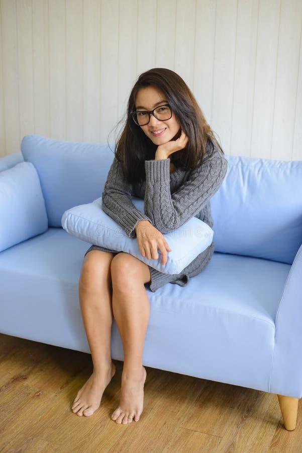 Mujer asiática que se sienta en el sofá azul con la almohada en manos foto de archivo