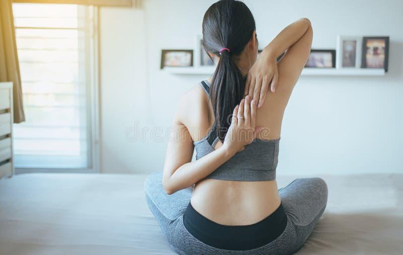 Mujer asiática que se sienta en la cama que practica haciendo el ejercicio de la yoga, entrenamiento después de despertar concept imagen de archivo