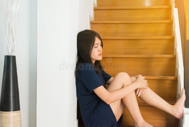 Mujer asiática que se sienta en las escaleras en casa, problema infeliz y confuso de la sensación femenina en la vida personal, c foto de archivo