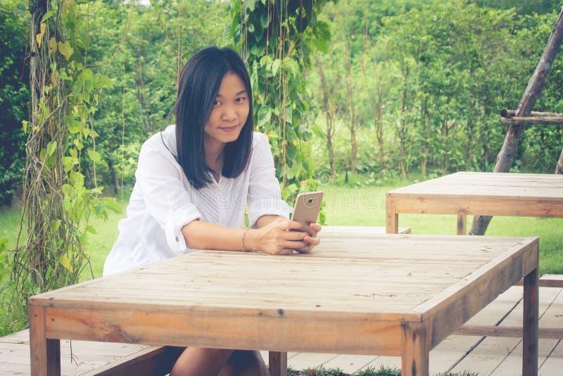 Mujer asiática que se sienta en silla de madera en el jardín al aire libre y que juega su smartphone fotos de archivo libres de regalías