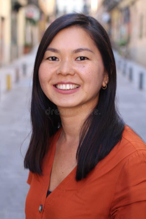 Mujer asiática que sonríe al aire libre headshot fotografía de archivo libre de regalías