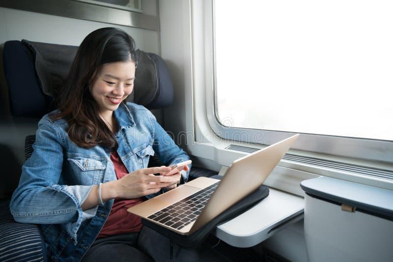 Mujer asiática que sonríe en el smartphone con el ordenador portátil en el tren, espacio de la copia en ventana fotos de archivo
