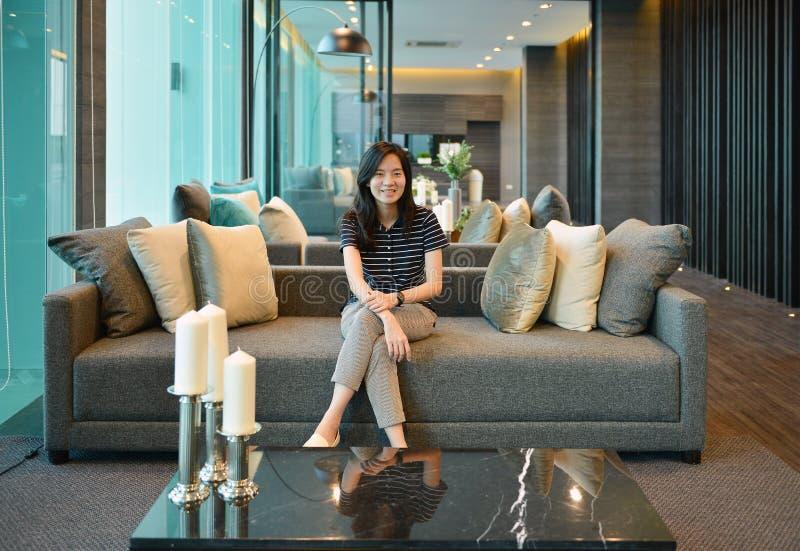 Mujer asiática que sonríe en el sofá en propiedad horizontal de lujo imagen de archivo libre de regalías