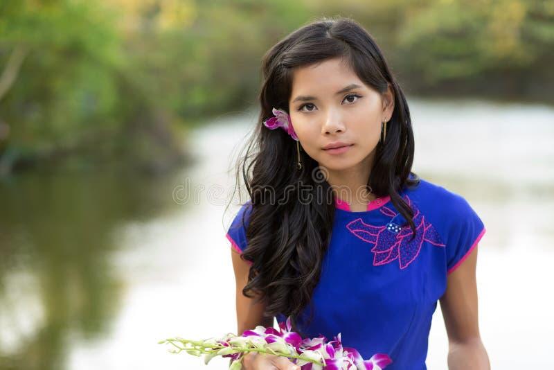 Mujer asiática que sostiene las flores frescas foto de archivo libre de regalías