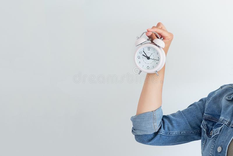 Mujer asiática que sostiene un despertador rosado en un fondo blanco El concepto de gestión de tiempo consiga el control de su vi foto de archivo libre de regalías