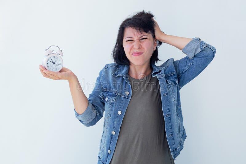 Mujer asiática que sostiene un despertador rosado en un fondo blanco El concepto de gestión de tiempo consiga el control de su vi imágenes de archivo libres de regalías