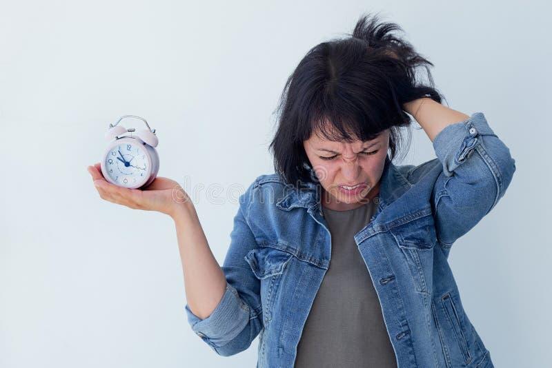 Mujer asiática que sostiene un despertador rosado en un fondo blanco El concepto de gestión de tiempo consiga el control de su vi fotos de archivo libres de regalías