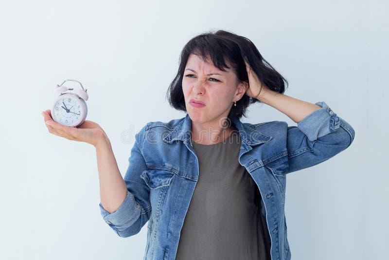Mujer asiática que sostiene un despertador rosado en un fondo blanco El concepto de gestión de tiempo consiga el control de su vi fotografía de archivo libre de regalías