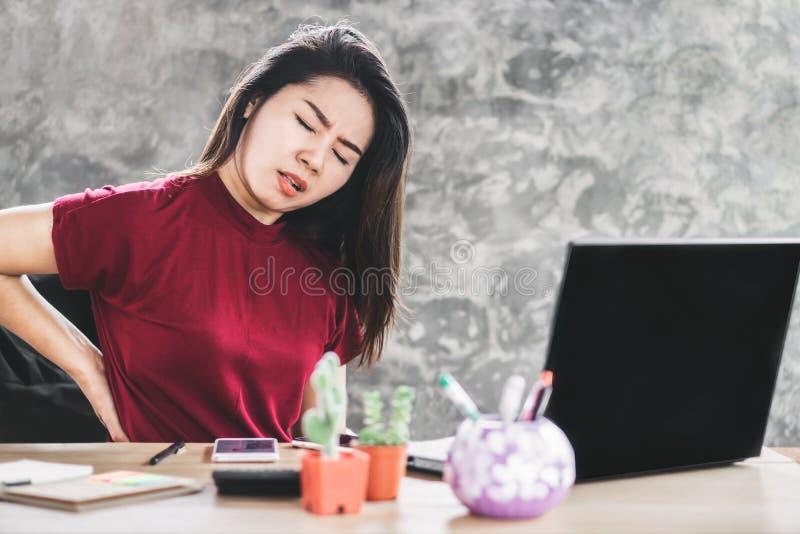Mujer asiática que sufre de un dolor más de espalda que sienta demasiado largo en la silla que trabaja en el ordenador imagen de archivo