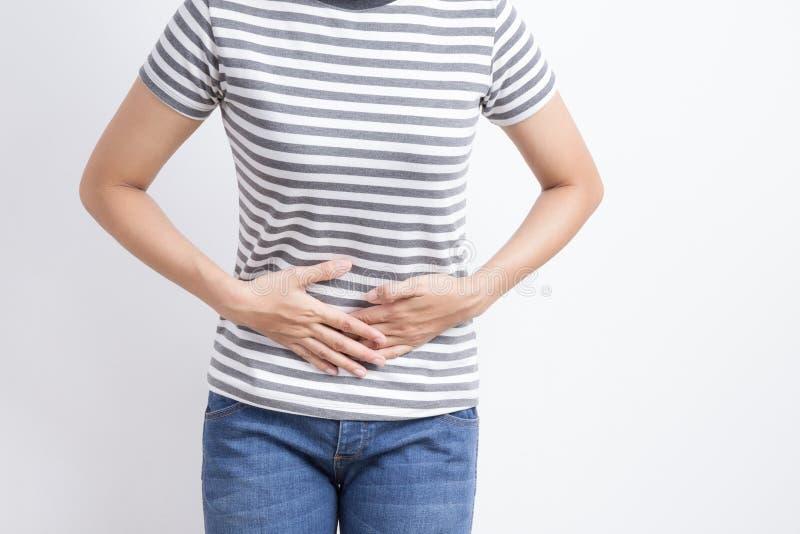 Mujer asiática que tiene dolor de estómago en el fondo blanco fotografía de archivo