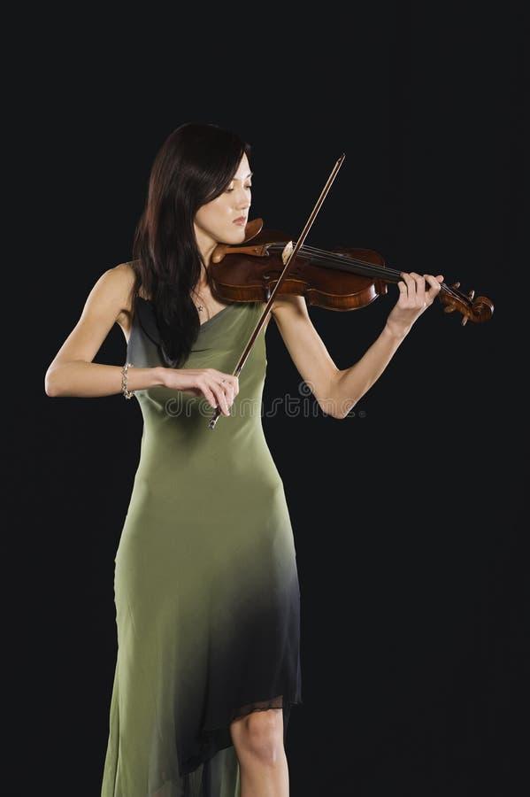 Mujer asiática que toca el violín imagen de archivo