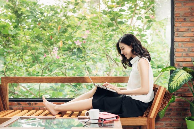 Mujer asiática que trabaja con el ordenador portátil mientras que se sienta cerca de ventana en cre foto de archivo libre de regalías