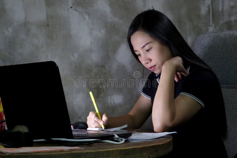 Mujer asiática que trabaja de hogar tarde en la noche imagenes de archivo