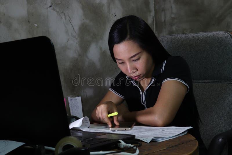 Mujer asiática que trabaja del hogar atrasado en el trabajo nocturno en concepto de iluminación pobre la luz oscura tiene cierto  imágenes de archivo libres de regalías