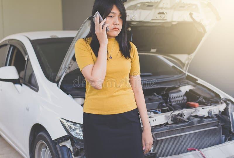 Mujer asiática que usa el móvil con el coche analizado foto de archivo