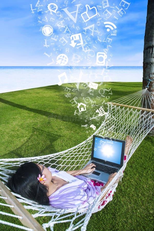 Mujer asiática que usa el ordenador portátil en la hamaca en la playa fotos de archivo libres de regalías