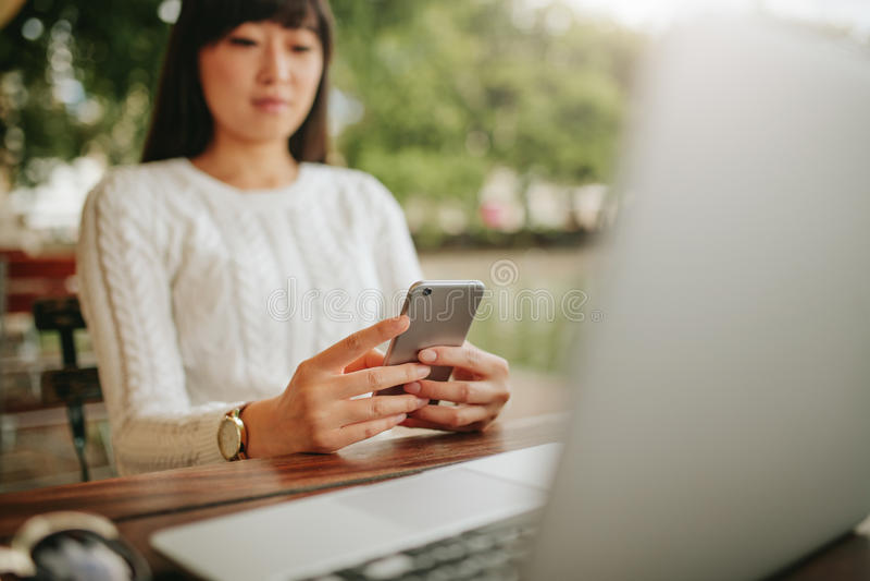Mujer asiática que usa el teléfono móvil en el café al aire libre imagen de archivo libre de regalías