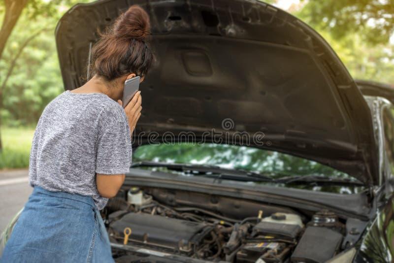 Mujer asiática que usa el teléfono móvil mientras que mira el coche analizado fotografía de archivo libre de regalías