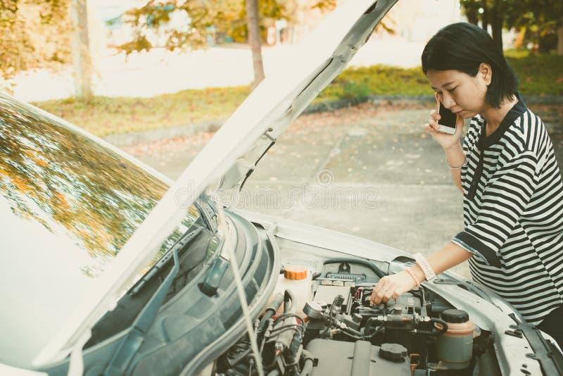 Mujer asiática que usa el teléfono móvil y pidiendo ayuda mientras que el coche analizado fotos de archivo libres de regalías